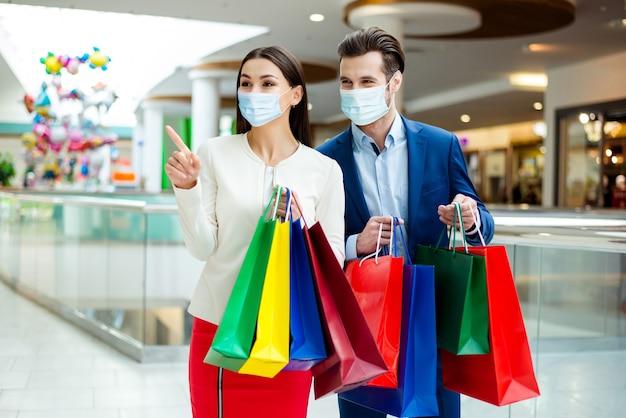 Gezond paar met gaasmasker lopen winkelcentrum boetiek draagtassen kiezen