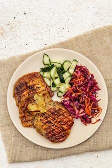 Gezond paleo-eten met gegrild vlees, verse komkommer, gefermenteerde kool en wortel