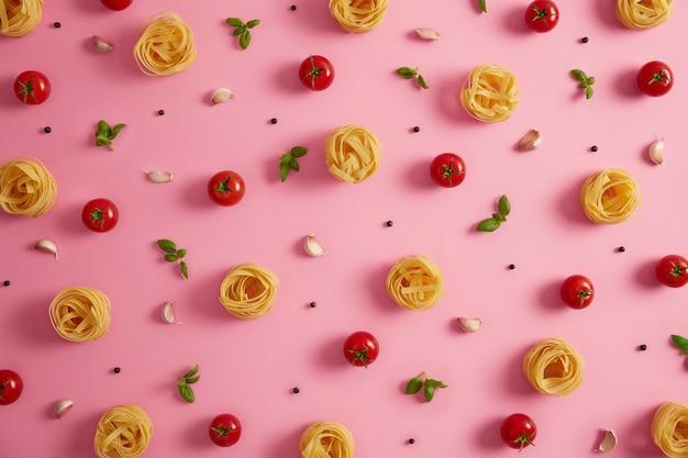 Gezond pastarecept en kookconcept. ongekookte glutenvrije pastanesten bevatten een goede hoeveelheid vezels en wat proteïne, rode kerstomaatjes, basilicum en knoflook op roze achtergrond. evenwichtige smakelijke maaltijd
