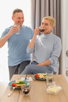 Gezond rijp paar drinkt koffie bij het ontbijt op een keuken die pratende en lachende vrouw glimlachen
