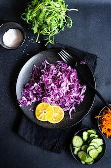 Gezond saladeconcept met ruwe en verse groente in een kom op zwarte concrete oppervlakte