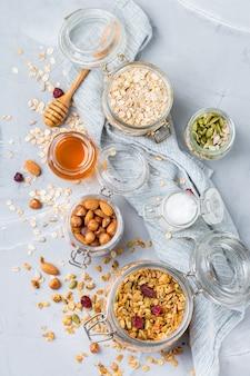 Gezond schoon eten, diëten en voeding, fitness, evenwichtige voeding, ontbijtconcept. zelfgemaakte muesli muesli met ingrediënten op een tafel. bovenaanzicht plat lag achtergrond
