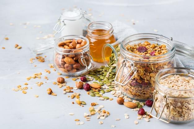 Gezond schoon eten, diëten en voeding, fitness, evenwichtige voeding, ontbijtconcept. zelfgemaakte muesli muesli met ingrediënten op een tafel. ruimte achtergrond kopiëren