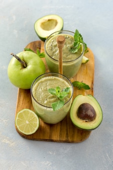 Gezond schoon eten, glazen mok met groene gezondheid smoothie van appel spinazie limoen en avocado op een tafel