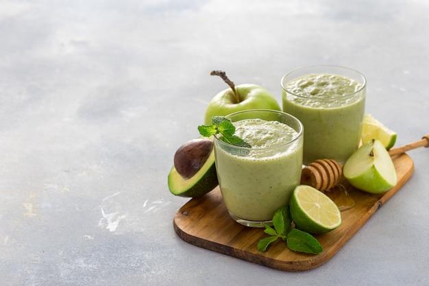 Gezond schoon eten, ontbijt groen sap smoothie van appel spinazie limoen avocado en honing op een tafel