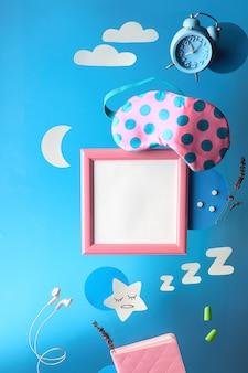 Gezond slaap creatief concept, tekstplaats, copyspace in frame. vliegend of zwevend slaapmasker, alarm, koptelefoon, oordopjes, pillen. papieren maan ster, wolken