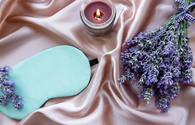 Gezond slaapconcept. lavendelboeket, slaapmasker en kaars op zijdeachtergrond
