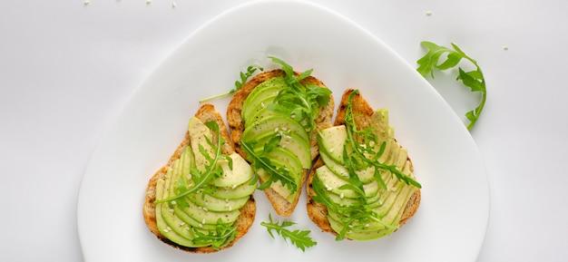Gezond snackconcept. toosts met avocado, garnalen en rucola op witte achtergrond. bovenaanzicht, platliggend.