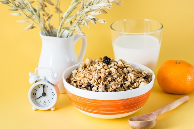 Gezond stevig ontbijt. gebakken granola van haver, noten en rozijnen in een kom, een glas melk, een sinaasappel en een wekker op een gele ondergrond