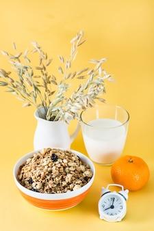 Gezond stevig ontbijt. gebakken muesli in kom, glas melk, sinaasappel en wekker op geel oppervlak. verticale weergave