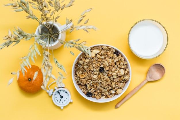 Gezond stevig ontbijt. gebakken muesli in kom, glas melk, sinaasappel, houten lepel en wekker op geel oppervlak. bovenaanzicht