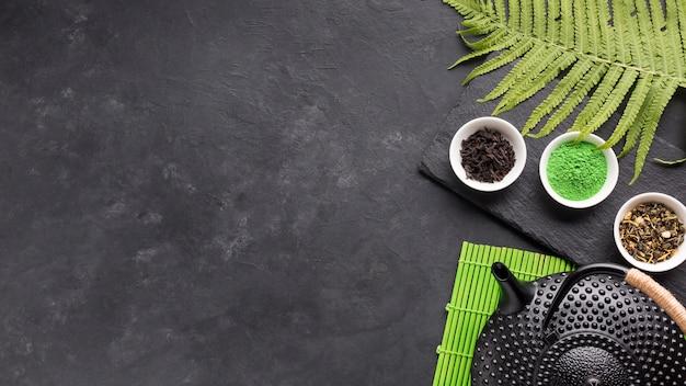 Gezond theeingrediënt met zwarte theepot en varenbladeren over achtergrond