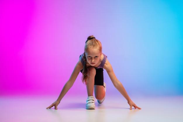 Gezond. tienermeisje, professionele atleet, jogger in actie, beweging geïsoleerd op een roze-blauwe achtergrond met kleurovergang in neon licht. concept van sport, beweging, energie en dynamische, gezonde levensstijl.