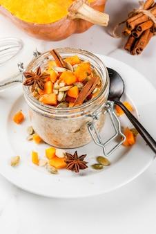 Gezond veganistisch eten. dieetontbijt of snack. pompoenpastei 's nachts haver, met pompoen, yoghurt, kaneel, kruiden. in een glas, op een witte marmeren tafel. kopieer ruimte