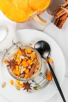Gezond veganistisch eten. dieetontbijt of snack. pompoentaart 's nachts haver, met pompoen, yoghurt, kaneel, kruiden. in een glas, op een witte marmeren tafel. kopieer ruimte bovenaanzicht