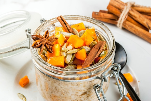 Gezond veganistisch eten. dieetontbijt of snack. pompoentaart 's nachts haver, met pompoen, yoghurt, kaneel, kruiden. in een glas, op een witte marmeren tafel. kopieer ruimte