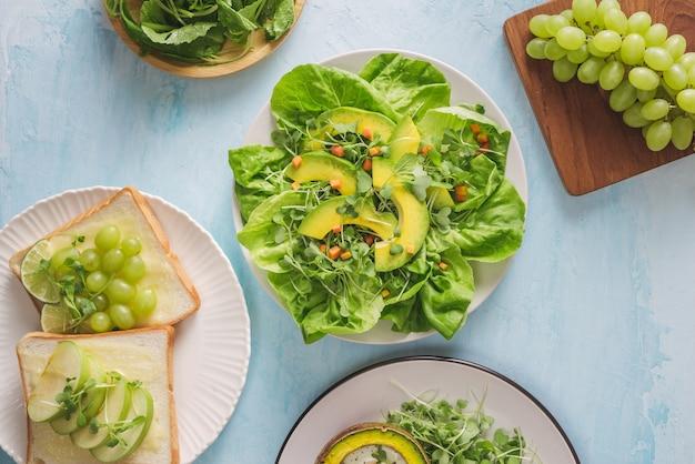Gezond veganistisch ontbijt. eetpatroon. gebakken avocado met ei en frisse salade van rucola, toast en boter. op een witmarmeren plaat een lichte betonnen tafel. een kopje koffie. ruimte kopiëren