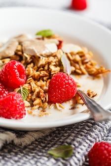 Gezond veganistisch ontbijt - gebakken havermoutkruimeltaart met bessen en notenboter in een witte plaat.