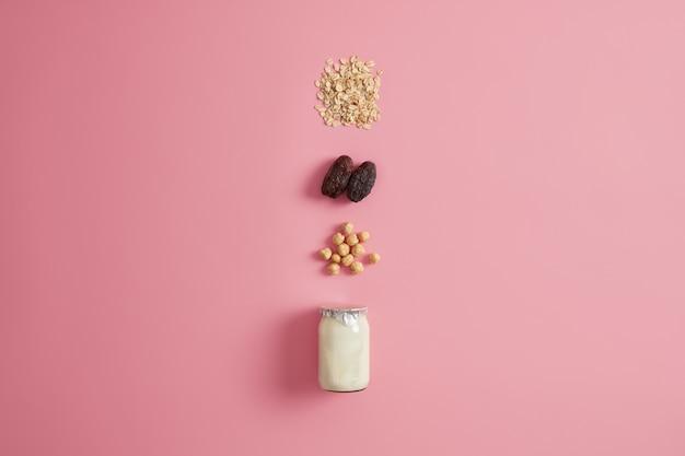 Gezond vegetarisch eten en ochtendvoeding concept. zelfgemaakte yoghurt met biologische ingrediënten, hazelnoot, gedroogde dadels en havergranen voor het bereiden van pap. dieet ontbijt. havermoutproducten