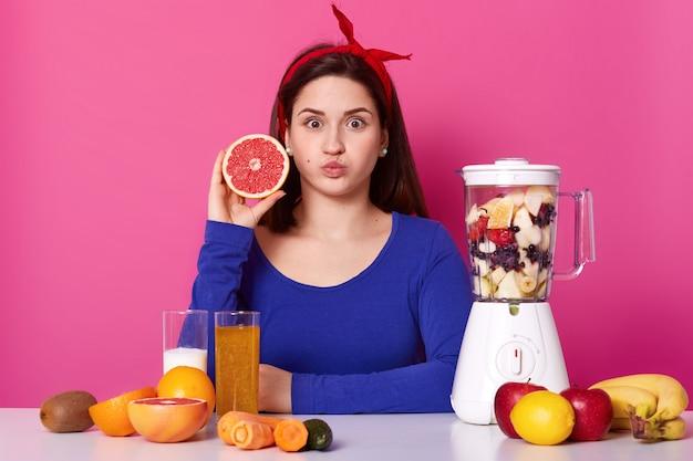 Gezond vegetarisch meisje opent wijd haar ogen, blaast haar mond, kijkt rechtstreeks naar de camera en houdt fruit in één hand. verschillende fruit is op tafel en in de blender, heerlijke smoothie koken.