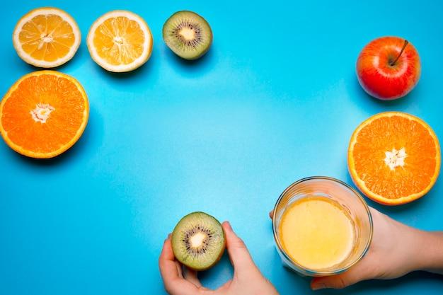 Gezond vers fruit en sap op de blauwe achtergrond. sinaasappel, citroen, kiwi, appel. vrije ruimte voor tekst. kleurrijke plat lag. gezonde levensstijl of voedingsconcept.