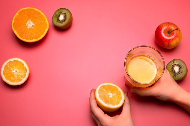 Gezond vers fruit en sap op de roze achtergrond. sinaasappel, citroen, kiwi, appel. vrije ruimte voor tekst. kleurrijke plat lag. gezonde levensstijl of voedingsconcept.
