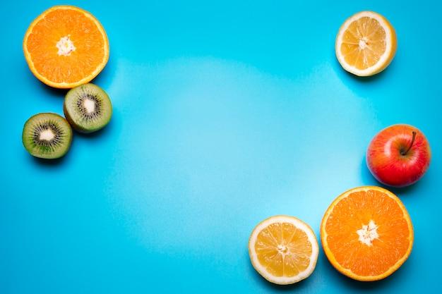 Gezond vers fruit op de blauwe achtergrond. sinaasappel, citroen, kiwi, appel. vrije ruimte voor tekst. kleurrijke plat lag. gezonde levensstijl of voedingsconcept.