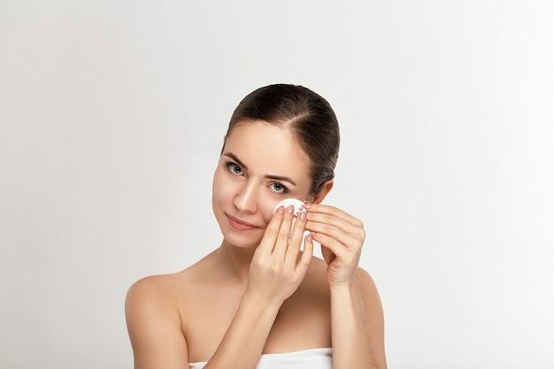 Gezond vers meisje make-up verwijderen uit haar gezicht met wattenschijfje