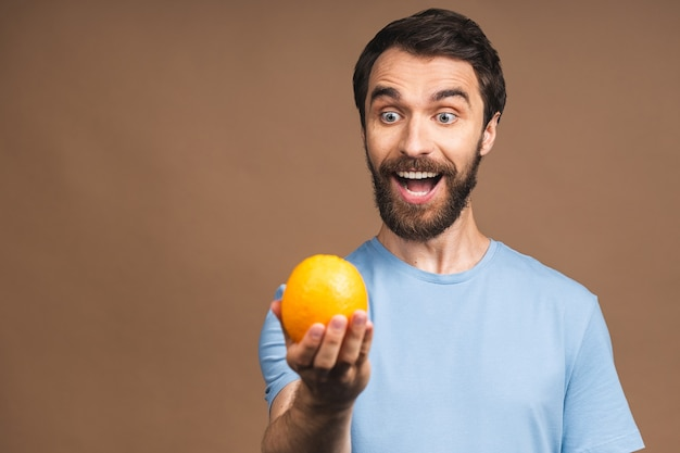 Gezond voedsel en dieetconcept. portret van jonge, bebaarde glimlachende man met een oranje fruit geïsoleerd op beige achtergrond.