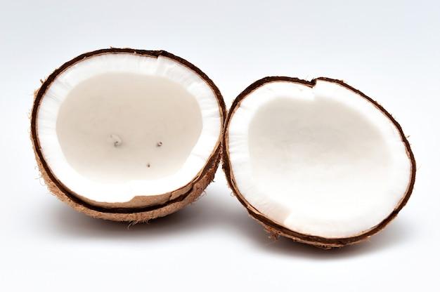 Gezond voedsel - gehalveerde kokosnoot die op witte achtergrond wordt geïsoleerd.