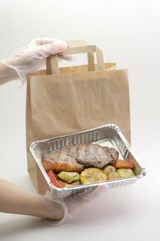 Gezond voedsel in een foliedoos, zorgvuldige levering, gehandschoende handen van vrouwen die voedsel op een geïsoleerde muur houden