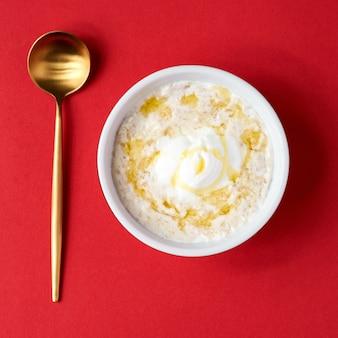 Gezond voedsel klassieke pap in witte kom op rode muur, selectieve aandacht. havermout gecombineerd met ontbijtgranen.