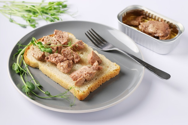 Gezond voedsel, sandwich met levertraan en erwten microgrines op een grijze plaat op een witte achtergrond