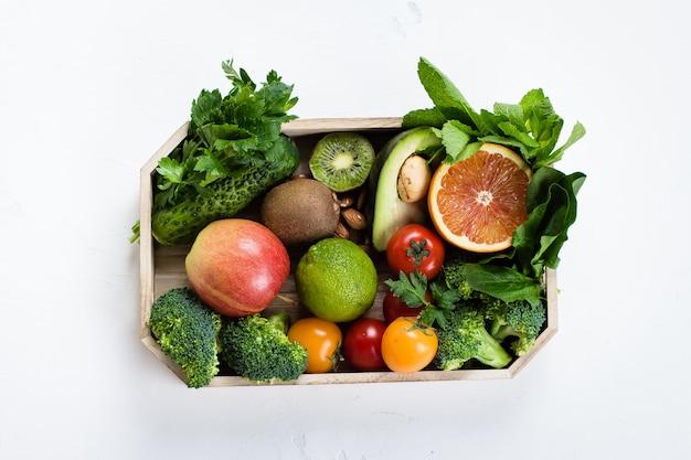 Gezond voedsel schoon. rauwe vruchten, groenten, noten, granen in houten lade op concrete achtergrond.