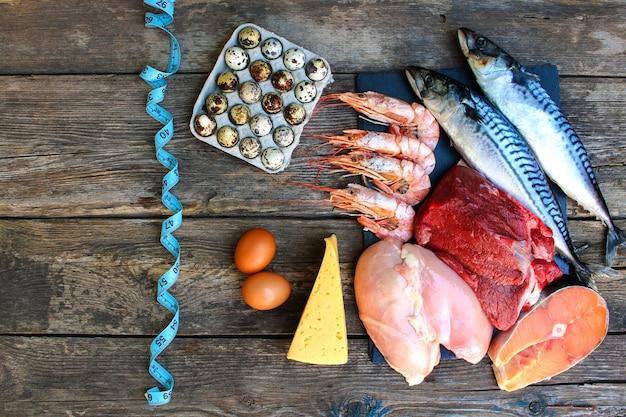 Gezond voedsel van dierlijke oorsprong op oude houten tafel. concept van goede voeding. bovenaanzicht. plat liggen.