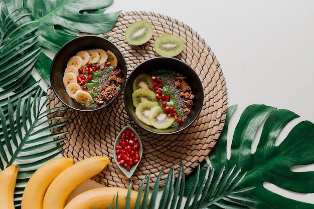 Gezond voedselconcept. bovenaanzicht op tafel met smoothiekommen. bord gegarneerd met kiwi, granola, granaat, chia, avocado.