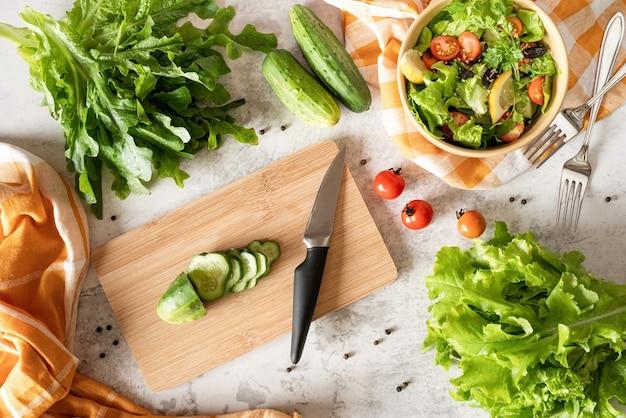 Gezond voedselconcept. bovenaanzicht van het maken van groentesalade met snijplank, kom met salade en verse biologische groenten