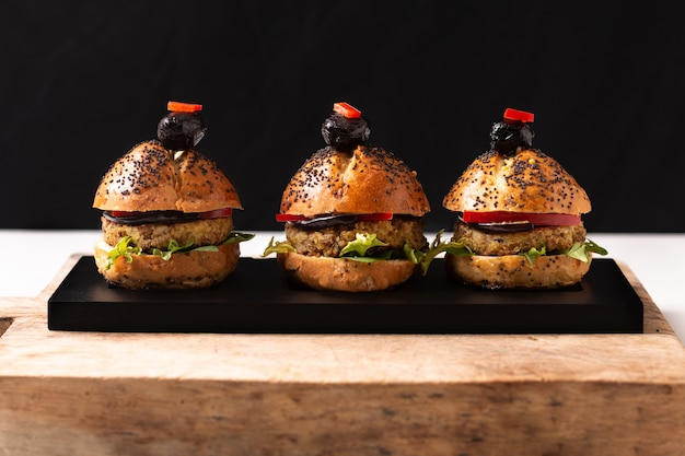 Gezond voedselconcept eigengemaakte veganistquinoa hamburgers op de zwarte plaat met exemplaarruimte