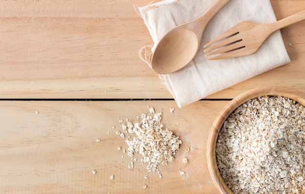 Gezond voedselconcept. havermout in houten kom op oude tafel