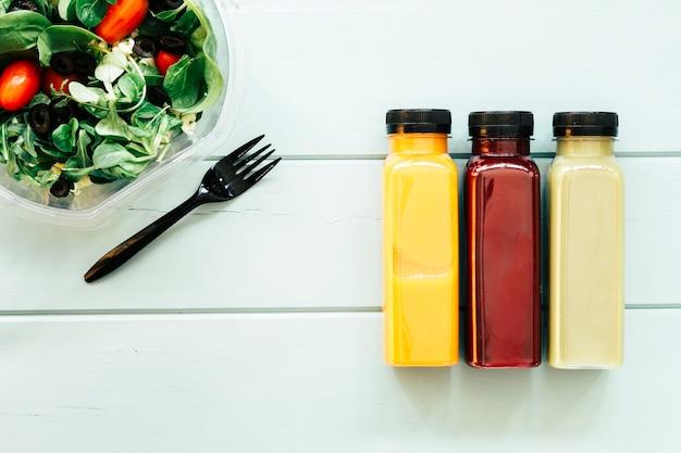 Gezond voedselconcept met sappen en salade