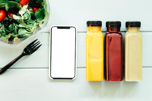 Gezond voedselconcept met smartphone naast sappen