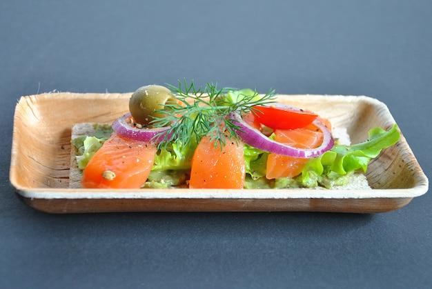 Gezond volkoren knäckebröd met avocadopasta, zalm, olijven, ui, tomaten. gezonde voeding schotel