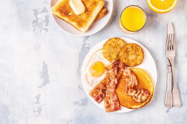 Gezond volledig amerikaans ontbijt met eieren, spek, pannenkoeken en latkes, bovenaanzicht.