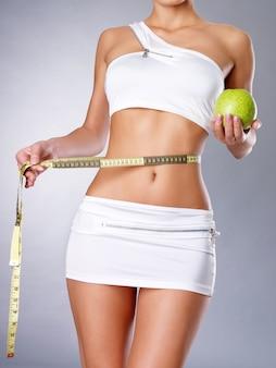 Gezond vrouwelijk lichaam met appel en meetlint. gezond fitness en eetlevensstijlconcept.