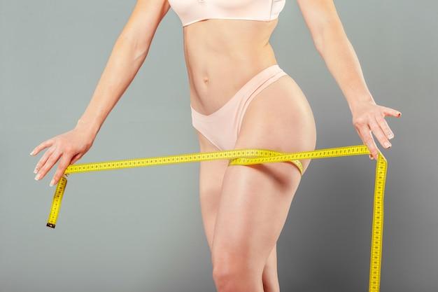 Gezond vrouwelijk lichaam met meetlint