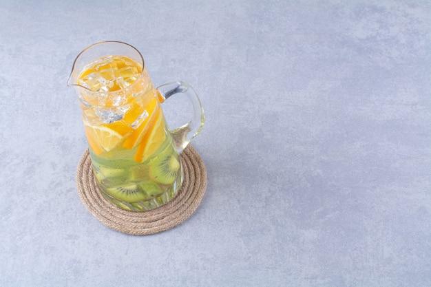 Gezond vruchtensap in een karaf op marmeren tafel.
