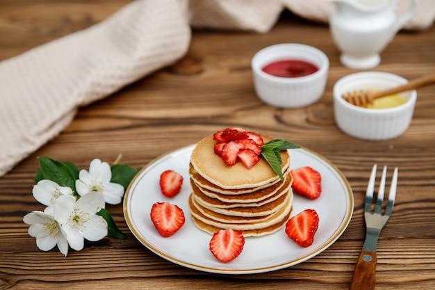 Gezond zomerontbijt, zelfgemaakte klassieke amerikaanse pannenkoeken met verse bessen en honing op een houten achtergrond. heerlijke gebakjes, dessert.