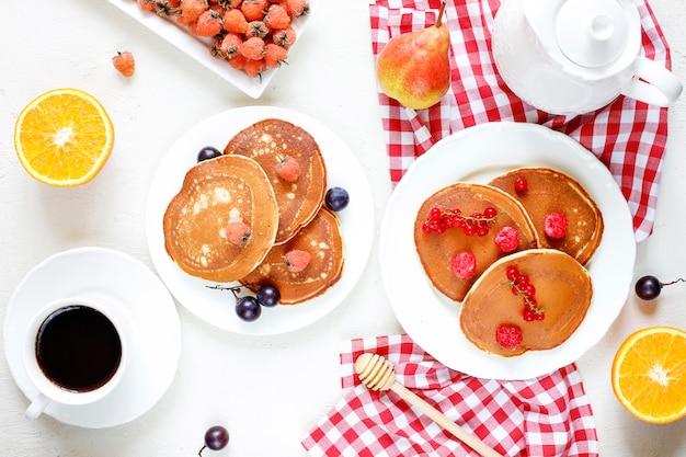 Gezond zomerontbijt, zelfgemaakte klassieke amerikaanse pannenkoeken met verse bessen en honing