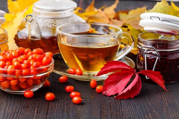 Gezonde achtergrond. wilde bessen en frambozenjam, honing en thee op val houten tafel