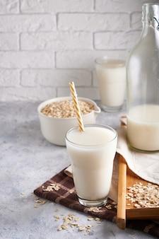 Gezonde alternatieve melk. zelfgemaakte eikenmelk in glas en fles op lichte tafel lactose vrij